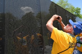 An Alabama veteran takes a snapshot of the name of a fallen friend's name on the Vietnam Wall. (Donna Cope/Alabama NewsCenter)