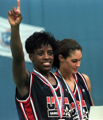 The captain of the USA women's basketball team, Ruthie Bolton-Holifield gives the winning salute on the medal stand after the USA beat France to win the gold at the 1994 Goodwill Games in St. Petersburg, Russia. At right, Jennifer Azzi, of the USA, studies her medal certificate. (Holly Stein/ALLSPORT)
