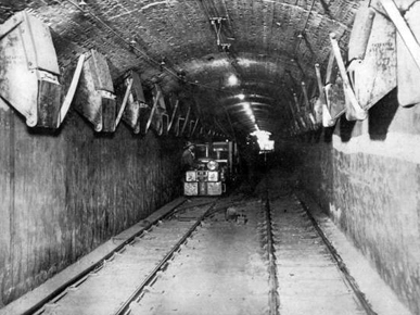An electric tram moves through a tunnel of the Warner Coal Mines in Birmingham, ca. 1908. Miners fed coal from the mine shafts into chutes, where it emerged from the hatches that lined the tunnel. It then was transported to the surface by trams pulled by the train engine. (From Encyclopedia of Alabama, courtesy of Birmingham Public Library Archives)