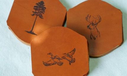 Andrew Lee's images of alabama flora and fauna stamped onto leather coasters. (Mark Sandlin/Alabama NewsCenter)
