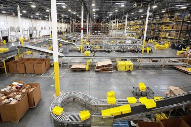 Plastic crates move along a conveyor at an Amazon.com Inc. fulfillment center. A similar facility is being built in Bessemer. (Bess Adler/Bloomberg)