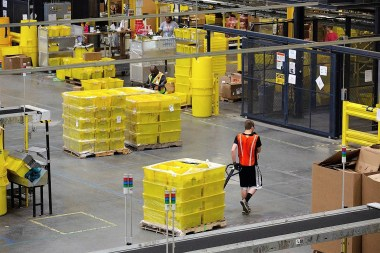 An employee pulls a pallet jack carrying plastic crates containing online orders at the Amazon.com Inc. fulfillment center in Robbinsville, New Jersey. (Bess Adler/Bloomberg)