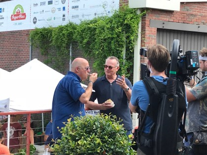 A camera crew films Andrew Zimmern's and Frank Stitt's food-sampling trek through the Market at Pepper Place for one of Zimmern's television shows. (Michael Sznajderman/Alabama NewsCenter)