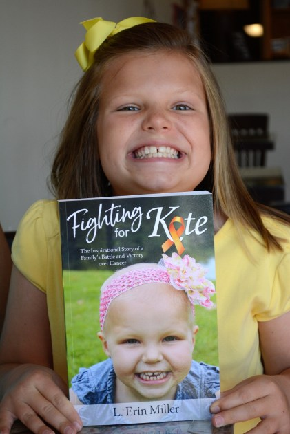 "Kate Miller, cancer-free for about five years, matches her grin on the cover of ""Fighting for Kate."" (Karim Shamsi-Basha/Alabama NewsCenter)"