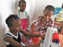 Children examine a sewing machine in the Maasai Chic sewing room in Tanzania. (contributed)