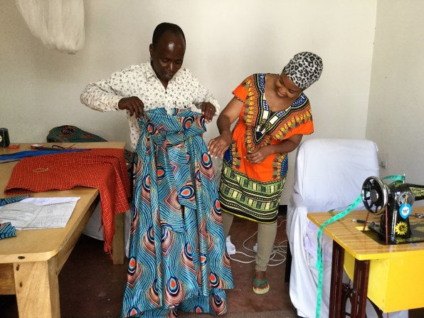 A Tanzanian woman displays the dress she is making to Maasai Chic's Stacey Scott. (contributed)