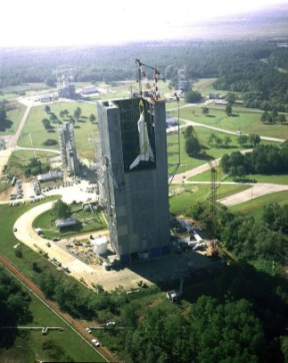 This aerial view of the shuttle Enterprise shows the shuttle orbiter being hoisted into Marshall's Dynamic Test Stand for the Mated Vertical Ground Vibration test. The test marked the first time that the entire space shuttle -- an orbiter, an external tank and two solid rocket boosters -- were mated together, Oct. 4, 1978. (Earnie Harding, NASA)
