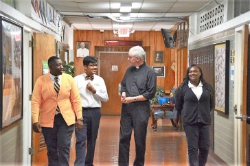 Father Jon Chalmers hangs with a few students at Holy Family Cristo Rey Catholic High School. (Karim Shamsi-Basha / Alabama NewsCenter)