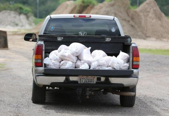 Saraland Public Works employees distribute free sandbags to residents in preparation of inland flooding associated with Tropical Storm Gordon on Tuesday in Saraland. (Mike Kittrell / Alabama NewsCenter)