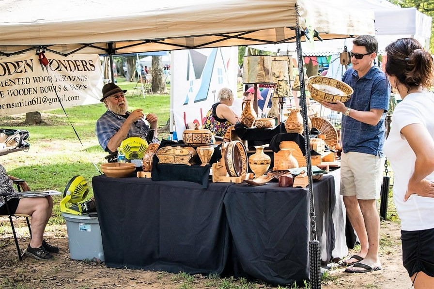 Shoppers enjoy speaking with Ben Smith, a local artist who offers wood turned functional art at his Wooden Wonders booth at Tinglewood Festival. (Fotowerks Custom Photography)