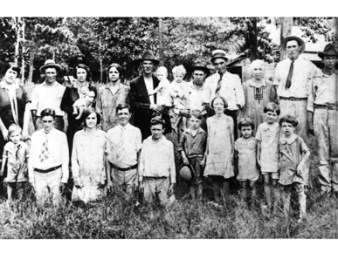 "In a photograph taken at a family reunion, c. 1925, young Hiram ""Hank"" Williams stands, far left, in front of his mother, Lillie Williams. (From Encyclopedia of Alabama, courtesy of Hank Williams Boyhood Home/Museum)"