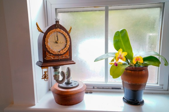 Jason Burnett takes time to find just the right combination of materials before he creates one of his delightfully whimsical clocks. (Mark Sandlin/Alabama NewsCenter)