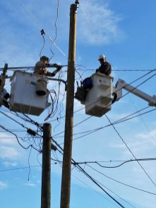 Denney (left) and Eldred work carefully as they make power line repairs. (Leah Cookston)