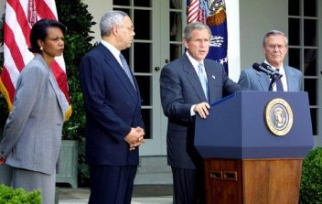 U.S. President George W. Bush (at podium) discusses his plan for peace in the Middle East as National Security Advisor Condoleezza Rice (left), Secretary of State Colin Powell (center) and Secretary of Defense Donald Rumsfeld (right) stand by his side in the White House Rose Garden on June 24, 2002. (White House, Wikipedia)