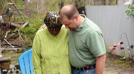 Gary Griffin prays with a Gordon resident after Hurricane Michael tore up the Houston County town. (Karim Shamsi-Basha/Alabama NewsCenter)