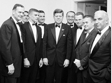 """U.S. President John F. Kennedy, center, poses with, from left, University of Alabama football coach Paul """"Bear"""" Bryant, White House Army Signal Agency John J. Cochran, All-American UA quarterback Pat Trammell, UA President Frank Rose, sportscaster Mel Allen, UA sports Hall of Famer Young Boozer Jr., Birmingham News sports writer Benny Marshall, and Alabama businessman Tom Russell at the Waldorf Astoria Hotel in New York City in December 1961. (From Encyclopedia of Alabama, courtesy of the John F. Kennedy Presidential Library and Museum)"""