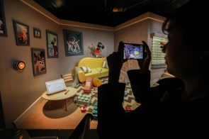 An attendee takes photos while on the Google Assistant Ride at the Google Assistant Playground. (Patrick T. Fallon/Bloomberg)