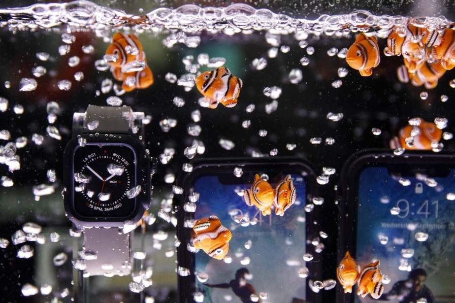 Plastic fish float next to Catalyst waterproof Apple Watch and iPhone cases displayed underwater during the CES Unveiled event. (Patrick T. Fallon/Bloomberg)