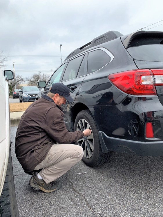 Ben Morris checks the air pressure in a tire. His FuelFox gasoline delivery service offers a full-service experience, including windshield washing and airing up any tires that need it. (file)