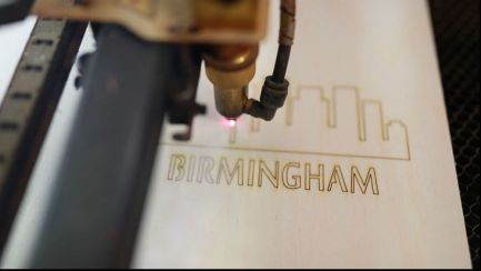 """A custom """"Birmingham"""" wood notebook comes together with high heat from the laser cutter. (Joe Allen)"""