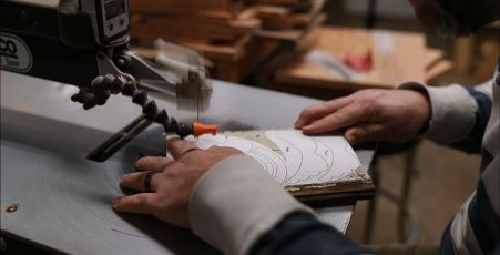 Maxcy works on his scroll saw, creating angel ornaments. (Joe Allen)