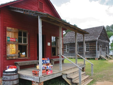 Landmark Park in Dothan is a living history museum that celebrates the heritage of Houston County, with emphasis on life at the turn of the 20th century. The site is home to a number of historic structures, including this store (foreground) and school (background). (From Encyclopedia of Alabama, courtesy of Landmark Park)