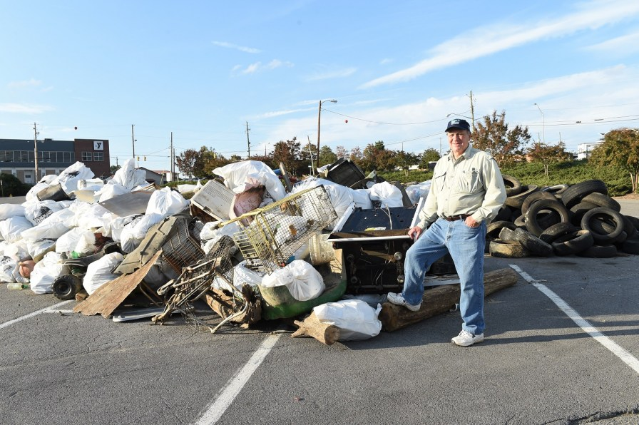 Gene Phifer poses with a mound of trash and debris collected from the water and shoreline during a Renew Our Rivers cleanup. (contributed)