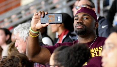 Jermaine Williams records as his daughter, Central Michigan junior Nadia Williams, competes in the long jump. (Solomon Crenshaw Jr./Alabama NewsCenter)