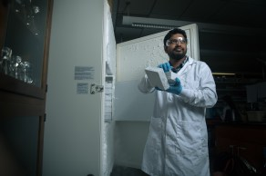 Graduate student Nayeem Bari removes a tube of bacteria from a freezer set to negative 112 degrees Fahrenheit. Bacteria stored at this temperature can be revived many years later. (University of Alabama)