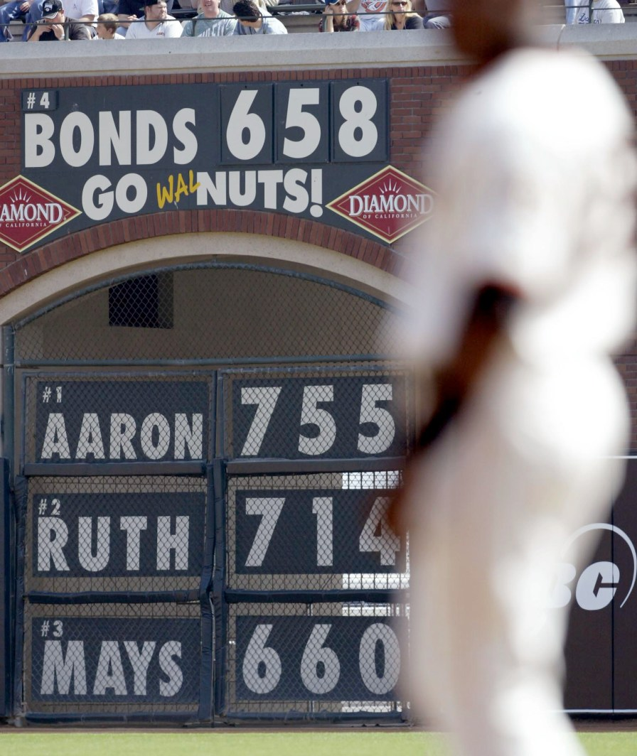 Barry Bonds of the San Francisco Giants walks by a sign that keeps count of the number of career home runs Bonds has hit, along with the career home run totals of Hank Aaron, Babe Ruth and Willie Mays, during a game against the Los Angeles Dodgers, Sept. 27, 2003. (Photo by Jed Jacobsohn/Getty Images)