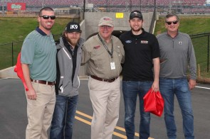 """NASCAR drivers Jeffrey Earnhardt (second from left) and Chase Briscoe (second from right) joined Talladega Superspeedway Chairman Grant Lynch (center), and Lance Taylor (far right) and Ellis Bennett (far left) from Taylor Corporation, who spearheaded the tunnel construction efforts, in the ribbon-cutting ceremony on Wednesday as part of the """"official"""" Grand Opening for fans to enter the track's iconic infield. (contributed)"""