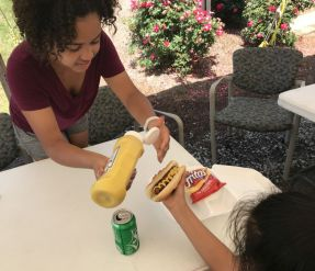A volunteer helps a child with her meal. (Donna Cope/Alabama NewsCenter)