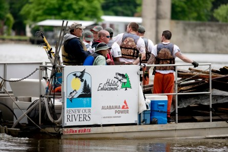 Renew Our Rivers volunteers carry debris and trash they have removed from the water. (Nik Layman/Alabama NewsCenter)