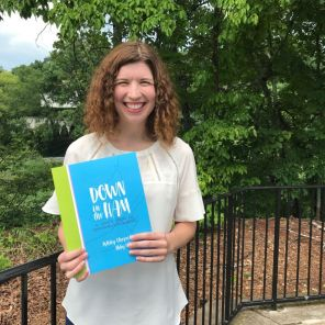 """Ashley holds """"Down in the Ham"""" and flips through the pages she brought to life with artist Abby Little Jessup. (Keisa Sharpe)"""