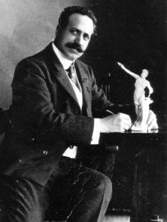 Guiseppe Moretti poses here with a model of his sculpture of Vulcan, commissioned in 1903 by the Commercial Club of Birmingham to represent Alabama at the 1904 World's Fair in St. Louis, Missouri. (From Encyclopedia of Alabama, Birmingham Public Library Archives)
