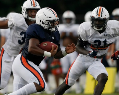 D.J. Willams runs while defenders Michael Harris, left, and Smoke Monday close in. (Todd Van Emst/AU Athletics)