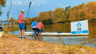 Salli O'Donnell gets help from her crew at the first portage. (Dennis Washington / Alabama NewsCenter)