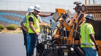 NASCAR driver Matt DiBenedetto helps pave a parking lot at Talladega Superspeedway. (Dennis Washington / Alabama NewsCenter)