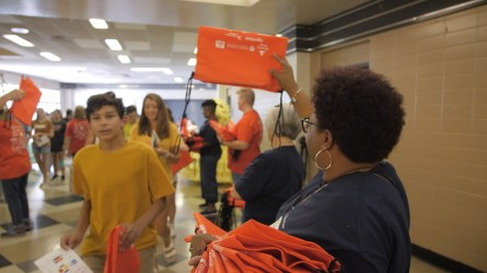 A volunteer provides a carry bag for students. (Dennis Washington / Alabama NewsCenter)
