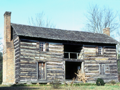 A two-story log dogtrot house with half-dovetail corners, owned by the St. Clair County Historical Society. The structure was built in the Beaver Creek valley ca. 1820 by the Looney family from Tennessee. It formerly was covered with siding which put it in the highest social and architectural category and it has unusual Flemish-bond brick chimneys, in which brick sides and ends alternate to form an interesting pattern. (From Encyclopedia of Alabama, courtesy of Eugene M. Wilson)