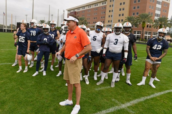 Auburn coach Gus Malzahn waits with the seniors as the team makes a tunnel to run through, celebrating its last practice at Auburn. (Todd Van Emst/AU Athletics)