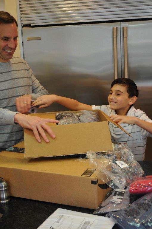 Alex Seligson prepares gifts for their Christmas Potluck lunch for the homeless with his son Braxton. (Karim Shamsi-Basha / Alabama NewsCenter)