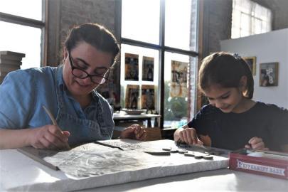 Gokden Alpman Matthews with daughter Zeynep Isabell Matthews and her studio in Huntsville's Lowe Mill A&E. (Brittany Dunn / Alabama NewsCenter)