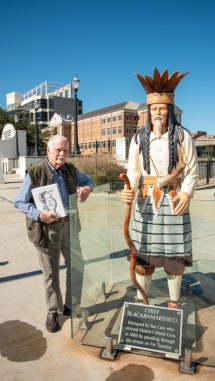 Wayne Dean stands in downtown Mobile next to a statue of Chief Slacabamorinico, a mythical character made famous by Joe Cain and remembered in Dean's book. (Dennis Washington / Alabama NewsCenter)