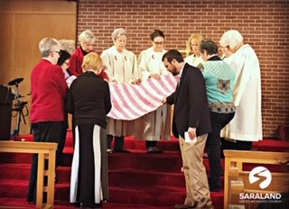 Members of Saraland United Methodist Church gather around a finished ground mat to pray. (contributed)