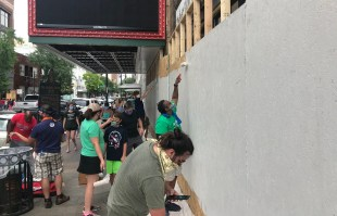 Volunteers on Sunday painted the boards temporarily covering the windows and doors of the Alabama and Lyric theaters in downtown Birmingham. (Michael Sznajderman/Alabama NewsCenter)