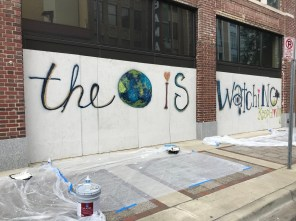 Volunteers paint an inspirational message on the boards covering the windows and doors of the Lyric Theatre. (Michael Sznajderman/Alabama NewsCenter)