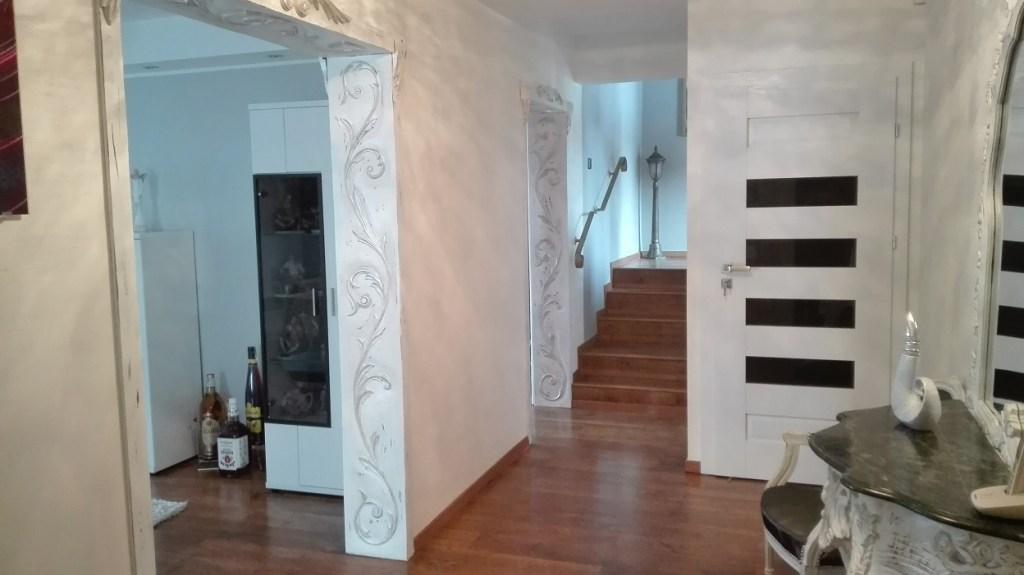 Rzeźbione futryny malowane na biało z przecierkami