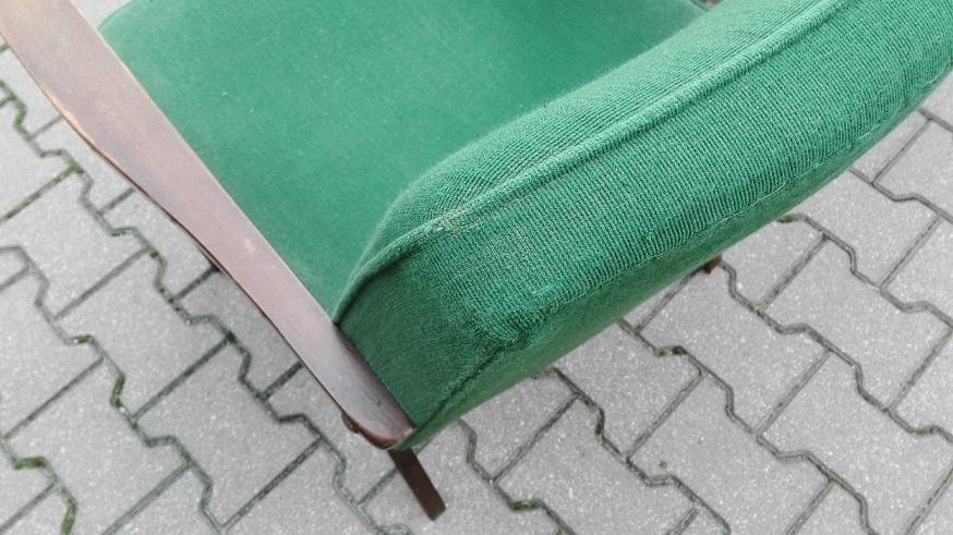 Stary fotel z zieloną tapicerką do wymiany