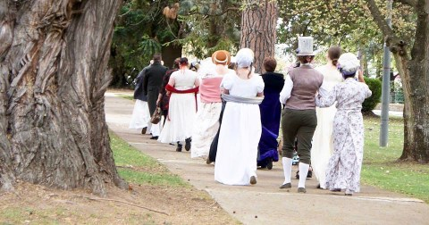 Rear view of a group of people in costume promenading in a park.